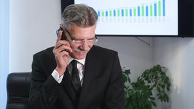 Businessman speaking on the phone in office in front of desktop Royalty Free Stock Image