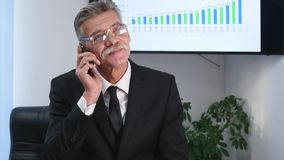 Businessman speaking on the phone in office in front of desktop Royalty Free Stock Images