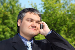 Businessman speaking by phone outdoor in summer Stock Image