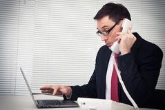Businessman speaking on phone, sitting at desk Royalty Free Stock Images