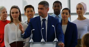 Businessman speaking on the podium with his colleagues in the business seminar 4k. Front view of a Caucasian businessman speaking to the public while standing on stock footage