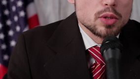 Businessman speaks into microphone. Flag of US behind speaker. The struggle will continue. Government shall protect citizens stock footage