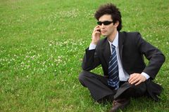 Businessman speaks by phone sitting on grass Stock Images