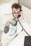Businessman speaks on phone, worries tie Royalty Free Stock Photo