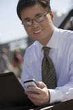 Businessman in spectacles using laptop and mobile phone, outdoors, smiling, portrait (tilt) Royalty Free Stock Image