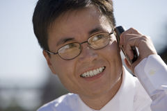 Businessman in spectacles using mobile phone, smiling, close-up Royalty Free Stock Image