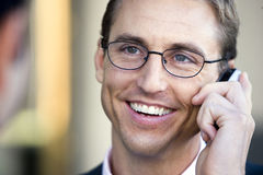 Businessman in spectacles using mobile phone, smiling, close-up (differential focus) Royalty Free Stock Photography