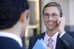 Businessman in spectacles using mobile phone, smiling, close-up (differential focus) Royalty Free Stock Photos