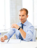 Businessman with spectacles writing in notebook Stock Photo