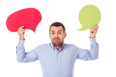Businessman with speech bubbles. Handsome businessman in smart casual wear is holding speech bubbles, looking at camera and showing dismay, isolated on white royalty free stock photos