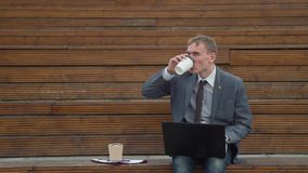 Businessman spilling coffee on himself outdoors stock video footage