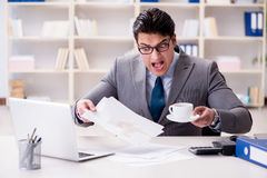 The businessman spilling coffee on important documents Stock Image