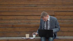 Businessman spilling his coffee while working stock video