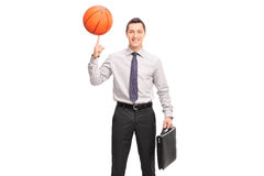 Businessman spinning a basketball on his finger. Cheerful young businessman holding a briefcase and spinning a basketball on his finger isolated on white Royalty Free Stock Photography