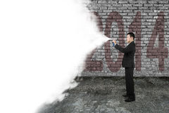 Businessman spray white cloud covering old 2014 dark brick wall Stock Photo