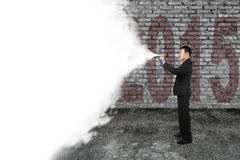 Businessman spray white cloud covering old 2015 dark brick wall Stock Images