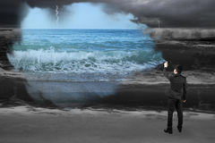 Businessman spraying calm sea paint covered dark stormy ocean Royalty Free Stock Photography