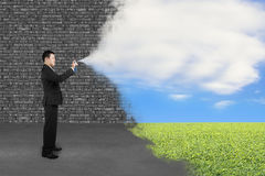 Businessman spraying clouds sky grass paint cover old brick wall Royalty Free Stock Image