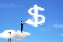 Businessman spraying dollar sign shape cloud paint with blue sky Royalty Free Stock Photo