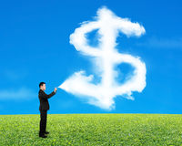 Businessman spraying dollar sign shape cloud paint with sky gras Stock Photo