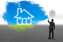 Businessman spraying house cloud sky grass paint covered gray ci Royalty Free Stock Photography