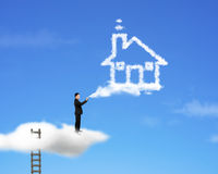 Businessman spraying house shape cloud paint with ladder and sky Stock Photography