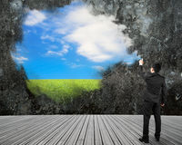 Businessman spraying sky cloud grass paint on dirty concrete wal Royalty Free Stock Image