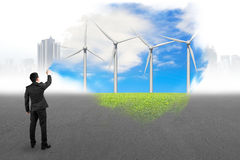 Businessman spraying wind turbines paint covered gray cityscape Stock Images