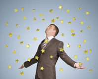 Businessman spread his arms. Gold stars fall from Royalty Free Stock Images