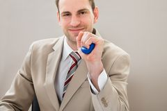 Businessman squeezing blue stressball Stock Photo