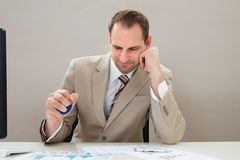 Businessman squeezing blue stressball Stock Photos