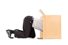 Businessman squeezing himself into a box Royalty Free Stock Photos