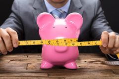 Free Businessman Squeezing Piggybank With Tape Measure On Table Royalty Free Stock Photo - 124525315