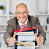 Businessman With Stack Of Books Gesturing Thumbs Up Royalty Free Stock Image