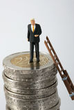 Businessman on a stack of coins Royalty Free Stock Photography