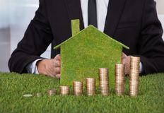 Businessman with stack of coins and eco friendly house. Businessman Holding Eco Friendly House In Front Of Stack Of Coins Over Grass Stock Photos