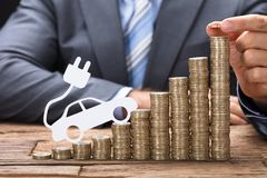 Businessman Stacking Coins With Electric Car At Table stock images