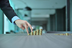 Businessman Stacking Coins in Increasing Order at desk Stock Photography