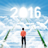 Businessman on the stairs with numbers 2016. Young businessman standing on the staircase while looking at clouds shaped number 2016 and future door Stock Photo