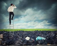 Businessman on a stairs searches far for clean environment. overcome the global pollution problem. Businessman on a stairs searches far for clean and green Royalty Free Stock Photo