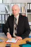 Businessman with stamp in the office is looking funny in to the Stock Image