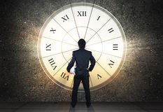 Businessman stand against sun light through clock glass Royalty Free Stock Photography