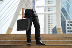 Businessman stand alone holding document bag at ladder after working Stock Images