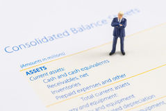 Businessman stand on the balance sheet Stock Photography