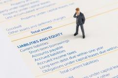 Businessman stand on the balance sheet Stock Photos