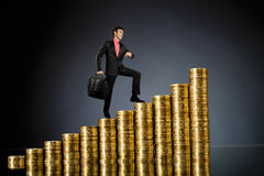 Businessman. Stand on top of  many rouleau gold  monetary  coin, on dark blue background Royalty Free Stock Photos