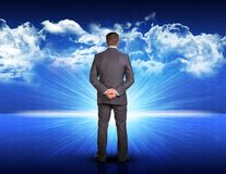 Businessman standing against blue landscape with Royalty Free Stock Images