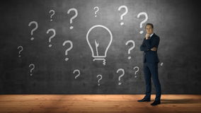 Businessman standing against question marks and bulb. On grey screen stock video footage