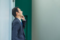 Businessman standing against wall using mobile phone and laughin Royalty Free Stock Photos
