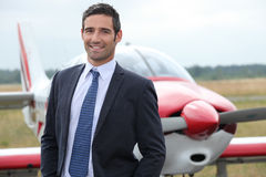Businessman standing by aircraft Stock Photography